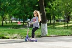 Kleine blonde Mädchenfahrt der Roller im Park Stockbilder