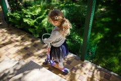 Kleine blonde Mädchenfahrt der Roller im Park Lizenzfreies Stockbild