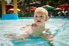 kleine blonde Mädchenhocken spricht im transparenten Wasser des Pools Lizenzfreie Stockfotografie