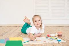 Kleine blonde Mädchenmalerei auf großem Weißbuch beim auf den Boden zuhause legen stockbild