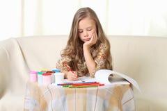 Kleine blonde Mädchenzeichnung zu Hause auf Sofa Lizenzfreie Stockbilder