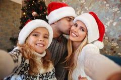 Kleine blonde Tochter in Sankt-` s Hut, der selfie während ihr PA nimmt Stockfotografie
