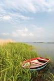 kleine boot bij een kust van een meer Stock Foto