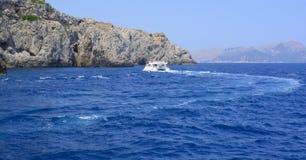 Kleine boot, blauwe oceaan en rotsachtige kust royalty-vrije stock fotografie