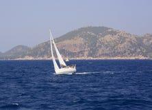 Kleine boot, blauwe oceaan en rotsachtige kust royalty-vrije stock foto