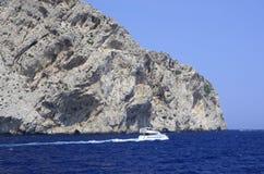 Kleine boot, blauwe oceaan en rotsachtige kust stock foto's