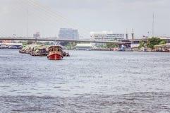 Kleine boot die commerciële aak op de rivier van chaophraya trekken Stock Afbeeldingen
