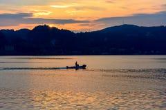 Kleine boot die op het water bij zonsondergang tegen de achtergrond van bergen en de het plaatsen zon drijven royalty-vrije stock afbeeldingen