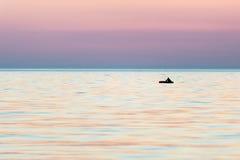 Kleine boot in het overzees bij zonsopgang stock afbeeldingen