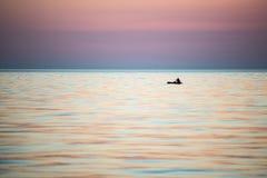 Kleine boot in het overzees bij zonsopgang stock foto