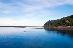 Kleine boot met mensen in stille binnenwaterenkusten van Vreedzame Oce Stock Afbeeldingen