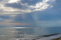 Kleine boot op de oceaan bij schemer Stock Fotografie