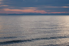 Kleine boot op de oceaan bij schemer Royalty-vrije Stock Foto's