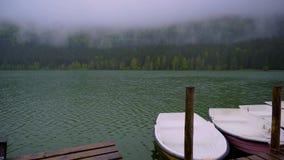 Kleine Boote, die auf den See nah an dem hölzernen Pier schwimmen Glatte ruhige Oberfläche von Gebirgssee Gebirgswald auf einem n stock video footage