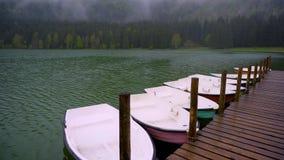 Kleine Boote, die auf den See nah an dem hölzernen Pier schwimmen Glatte ruhige Oberfläche von Gebirgssee Gebirgswald auf einem n stock footage