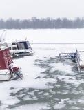 Kleine Boote eingeschlossen im Eis auf Fluss Donau Stockfotografie