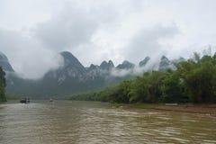Kleine boten en de cruiseschepen op Li-rivier in China Stock Foto's