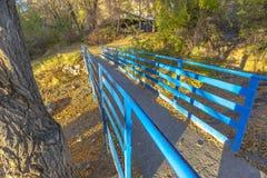 Kleine Brücke über dem blauen Geländer des Flusses exzentrisch lizenzfreie stockbilder