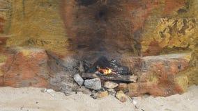 Kleine brand op het zand dichtbij de muur van gele shell rots Picknick op strand stock footage