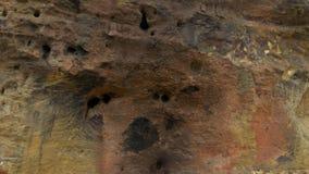 Kleine brand op het zand dichtbij de muur van gele shell rots Picknick op strand stock video