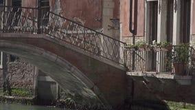 Kleine brug bij een kanaal in Venetië stock video