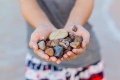 Kleine bunte Steine in der Hand auf Seeküstenunschärfe Stockbild