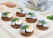 Kleine Canapes mit Heringen, Eiern und Schalotte Lizenzfreie Stockfotos