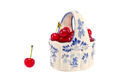 Ceramische mand met rode die kersen op wit worden geïsoleerdi Stock Foto's