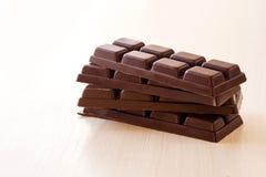 Kleine chocoladerepen die op elkaar op een lichte achtergrond worden gestapeld royalty-vrije stock fotografie