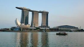Kleine cruiseboot en Marina Bay Sands bij de zonsondergang in Singapore stock videobeelden