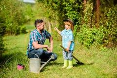 kleine de hulpvader van het jongenskind in de landbouw Ecolandbouwbedrijf vader en zoon in cowboyhoed op boerderij gieter, pot en royalty-vrije stock foto's