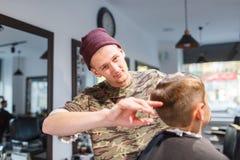 Kleine de jongenszitting van de kapperherenkapper parihopher strechot op een stoel Royalty-vrije Stock Afbeelding