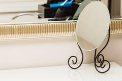 Kleine decoratieve spiegel voor vrouw op bureau Stock Afbeeldingen