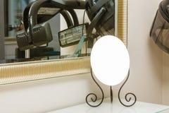 Kleine decoratieve spiegel voor vrouw op bureau Stock Foto's