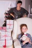 Kleine die jongen zeer over de giften voor Kerstmis binnen wordt opgewekt - moeder Stock Foto's