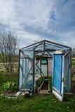 Kleine die serre met deuren in een tuin in de lente bij dag worden geopend royalty-vrije stock fotografie