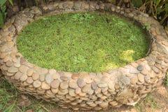 Kleine die tuinvijver van grintstenen wordt gemaakt Stock Foto