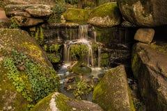 Kleine die waterval door rotsen wordt omringd Stock Afbeeldingen