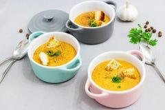 Kleine dienende potten of kommen met roomsoep die van rode linzen met beschuiten, kruiden en kruidenpeterselie, koriander wordt g stock foto