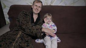 Kleine dochter met haar vader die op interessante film met grote emoties letten stock video