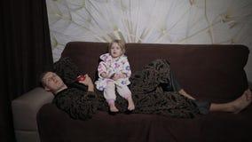 Kleine dochter met haar vader die op interessante film letten en appel eten stock video