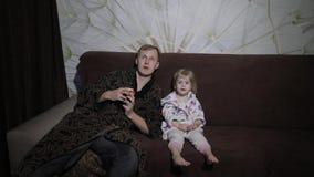 Kleine dochter met haar vader die op interessante film letten en appel eten stock footage