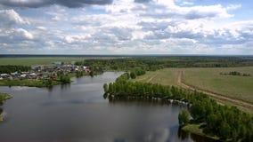 Kleine Dorfdächer auf ruhiger Flussbank nahe endlosen Feldern stock video