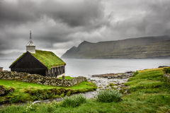 Kleine Dorfkirche unter schweren Wolken Stockfotografie