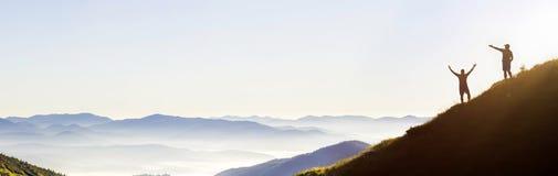 Kleine dunkle Schattenbilder von touristischen Reisenden auf steilem Berghang bei Sonnenaufgang auf dem Kopienraumhintergrund des stockfotos