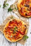 Kleine eigengemaakte plantaardige pizza met toevoeging van geroosterde peper, tomaten, kaas en kruiden op een witte houten lijst Royalty-vrije Stock Fotografie