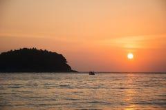 Kleine eiland en boot bij zonsondergang royalty-vrije stock afbeelding