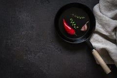 Kleine eingeteilte Bratpfanne auf einer schwarzen Steintabelle Dunkler kochender Hintergrund Stockbild