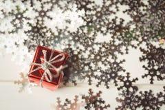 Kleine eingewickelte Geschenkbox und Schneeflocke zerstreuten auf Holztisch Stockfotografie