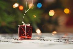 Kleine eingewickelte Geschenkbox und Schneeflocke zerstreuten auf Holztisch Lizenzfreie Stockfotos